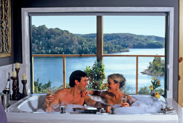 Two guests in a bubble-filled Jacuzzi, sipping champagne, with a huge picture window behind them with a mile-long view of Beaver Lake.