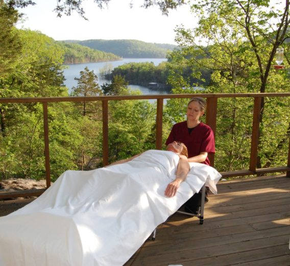 One of our professional masseuses gives a relaxing massage on the outside deck of a cabin with the peaceful scene of the lake and forest as the backdrop.