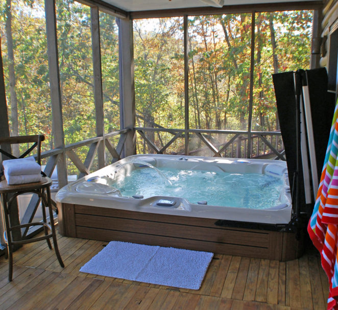 Sunbeams through the trees light up the crystal clear 10 person hot tub as it bubbles and jets. Colorful beach towels hang on the wall of the screened in porch that overlooks the lake.
