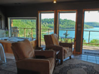 Two recliners in the foreground with emphasis on the lake view through the four large window that face Beaver Lake.