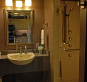 A vanity and the entrance to the roll in shower with 4-port body spray system in our accessible bathroom.