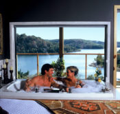 Two guests enjoying champagne in a warm, bubbling Jacuzzi with a mile-long view of Beaver Lake just behind them.