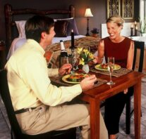 Two guests enjoying dinner with the bed and Jacuzzi in the background. We have either room service or catering with 24-hour advance notice.
