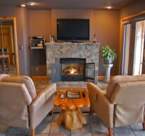 A warm fire in the native stone fireplace with the 4K TV above and two comfortable recliners in the foreground. The lake view is just to the right and can be seen anytime.