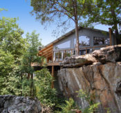 The front, glass wall and surrounding trees and bluffs of one of our Beaver Lake Cabins as seen from the exterior.
