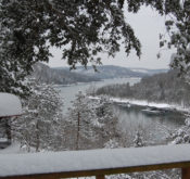 A snow-covered railing in the foreground underscores a winter wonderland with Beaver Lake in the distance.