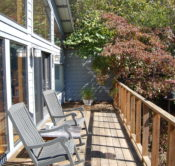 The sun deck of a Beaver Lake Cabin showing the front, glass wall, rocking chairs, and a dogwood tree shading the privacy wall.