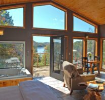 Looking out the front, glass wall onto Beaver Lake with the bed and chairs in the foreground with the lake framed in autumn leaves.