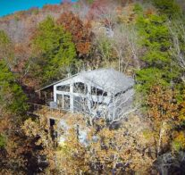 An aerial image of a cabin emerging from the autumn trees, its' lake-facing, front deck 20 feet off the ground due to the slope of the land. ground