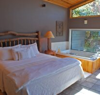 A king-size bed with luxurious linens sits next to a large, 2-person Jacuzzi and picture window looking out over Beaver Lake.