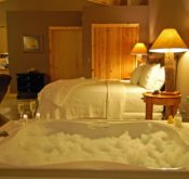 A night-time scene with a bubble-filled Jacuzzi with two champagne glasses awaits in the foreground with the king-size bed and nightstands behind.