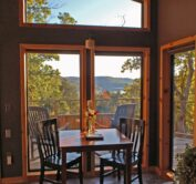 Late-afternoon light illuminates the cabin's dining table and its' forest-bounded view of Beaver Lake through the large, front wall windows.