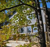 The front of the Bluff Cabin slightly obscured by fall foliage. The Bluff Cabin is surrounded by numerous, old hardwood trees that make fall a wonderful experience.
