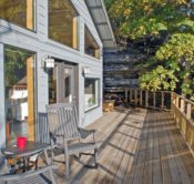 The front, glass wall and deck of the Bluff Cabin with the bluff and green and yellow fall leaves from a nearby oak tree in the background.