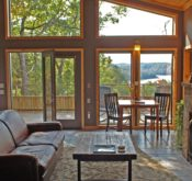 From right to left, the sofa, dining table, and native stone fireplace with a thick wood coffee table in the middle form the living area with the many windows of the front wall providing the view.