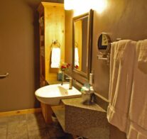 Warm light shines on the accessible lavatory, quartz counter-tops, personal mirrors, and natural pine cabinets of the bathroom.