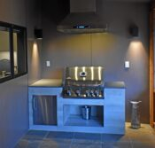 The built-in, stainless steel BBQ grill with lighted vent hood, quartz counter-tops, and pass-through window into the kitchen.
