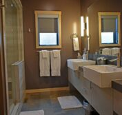 Looking into the stylish, modern bathroom with brushed, stainless steel fixtures, white overhanging sinks, gray cabinets with darker gray quartz counter-tops.
