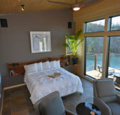 An interior view looking down on the 'art wall' on the left, king-size bed in the middle, and ten and a half foot high windows overlooking Beaver Lake and the suspended balcony.