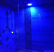 Blue light from the chroma-therapy lights illuminates the stream show with 4-port body spray system, kinetic shower head, and a rain-drop shower head as well.