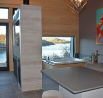 A view from the interior of the reading and Jacuzzi area with Beaver Lake visible through the windows and the dining table in the foreground.