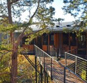 An exterior view of the rear of the Sky Suites showing the elevated walkway to the suites with mature cedar trees on either side and the Ozark Mountains in the background.