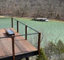 A view down onto one of the suspended, ipe (ironwood) decks of the Sky Suites complete with rocking chairs, fire table, and a commanding view of Beaver Lake.