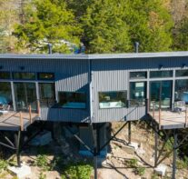 An exterior view of the lake-facing, front wall of this elevated, tree-house-like structure with each side sporting a 190 SF suspended deck with fire table.