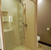 A modern deluxe walk-in shower with glass doors and stainless steel hardware.