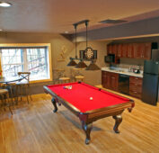 Looking into the lake house's downstairs game room equipped with red felt slate pool table and boars hair dartboard for hours of fun. A large kitchenette with full-sized fridge, microwave, dishwasher, and blender with bar tools all there for ease of enjoyment.