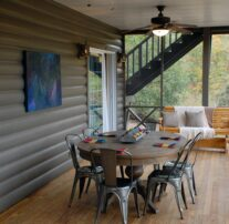 A large screened in porch where an outdoor dining table and rocking bench adorned with pillows and blankets are awaiting you along ceiling fans that provide a steady breeze.