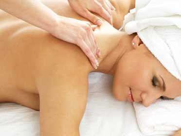 A women is peaceful as she gets a relaxing shoulder massage.