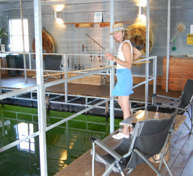 A guest fishing with a cane pole and enjoying a glass of wine in our indoor, heating fishing room.