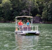 A happy couple enjoying a leisurely boat ride on our rentable mini electric pontoon featuring a shade canopy for relief on a hot sunny day.