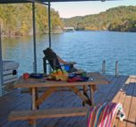 A women looks out at the rippled lake in an adorondack chair on the edge of the dock. A table under the covered area of the dock is set up for a nice picnic.