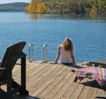 A women sits on the edge of our dock and dangles her feet in the cool clear water of Beaver Lake.