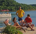 A group of guests relaxing on the sun deck as their extended family passes in a resort rental boat behind.
