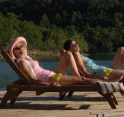 Two women sunbath on reclining lounge chairs and relax with margaritas as a pontoon boat floats along in the background.