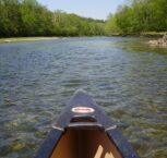 The tip of a canoe overlooks the White River with crystal clear waters and lush green foliage.