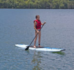 A women on a warm summer day enjoying one of our complimentary paddle boards on a calm day on Beaver Lake.