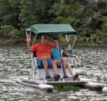 Two guests smiling and waving as they pedal along on Beaver Lake in our complimentary pedal boat.