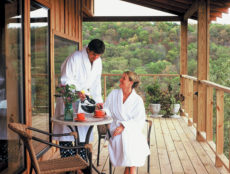 The covered, lake-facing, front decks of the Suites with two guests enjoying morning coffee in their bathrobes.