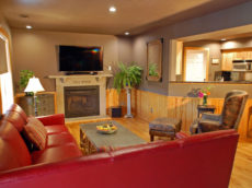 An open main floor living room has a rich red sectional couch and oversized cow print chair with ottoman that face a fireplace and 4K 3D 55