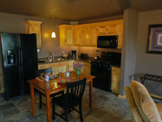 A dining table for two is set with a fully equipped kitchen behind.
