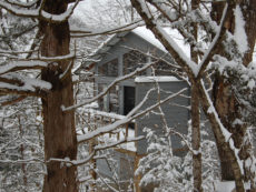 The front of a snow covered cabin peeks through white, frosted trees the morning after a snow fall back in 2009.