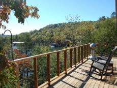 The front deck of a cabin over looking Beaver Lake on a sunny day complete with rocking chairs and a BBQ.