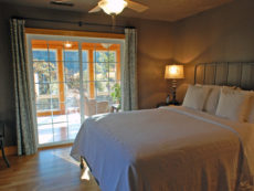 Blackout curtains are drawn in an intimate queen bedroom on the main floor at the Lake House featuring large sliding glass doors that can open up to the inviting lounge area of the sunroom.