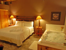 The king-size bed and the bubble-filled, 2-person Jacuzzi in our Bluff Cabin in the evening.