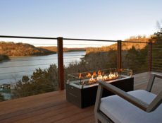 A scene from the elevated, front deck of a sky suite with the fire table in the foreground and Beaver Lake and the Ozark Mountains providing an amazing view.