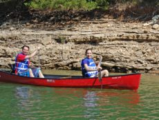 A handsome young couple with smiles on their faces row along the shelf rock lined shores of Beaver Lake on a warm sunny day.